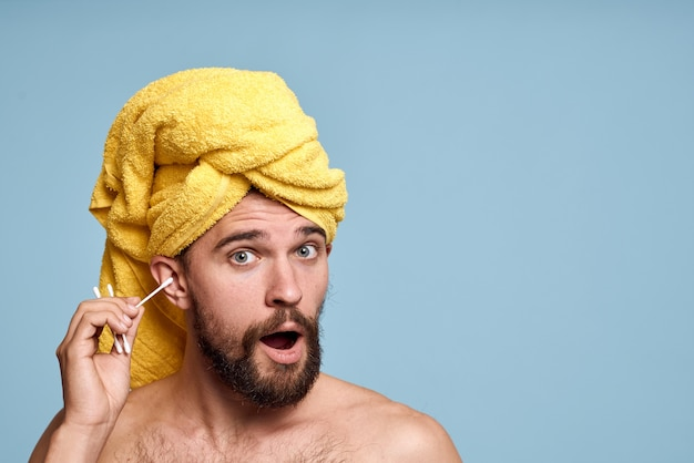 彼の頭の綿棒の衛生管理に裸の肩の黄色いタオルを持つ美しい男。