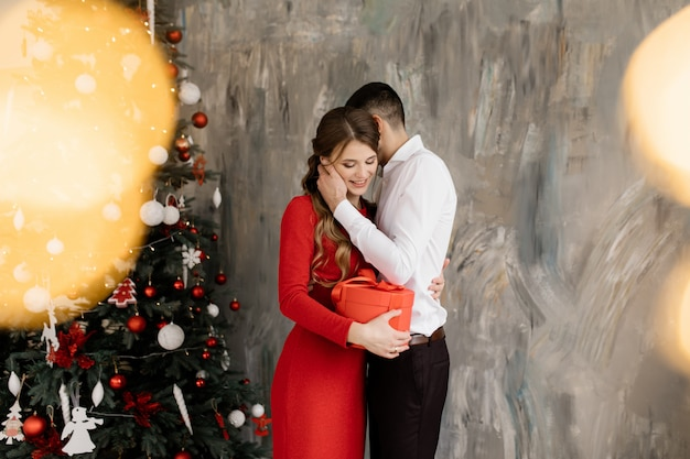 Beautiful man and woman in fancy closes pose before rich decorated christmas tree and exchange their