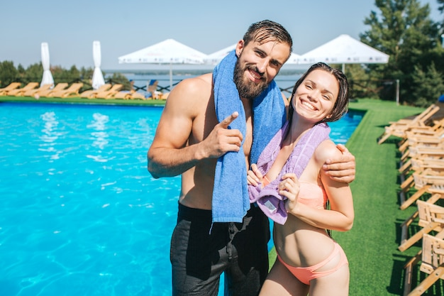 Beautiful man and woman stands at the edge of swimming pool and look  . they pose and smile. girl and guy have towels around their necks. they look happy.