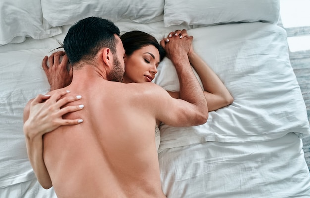 The beautiful man and woman in underwear having sex in the bed