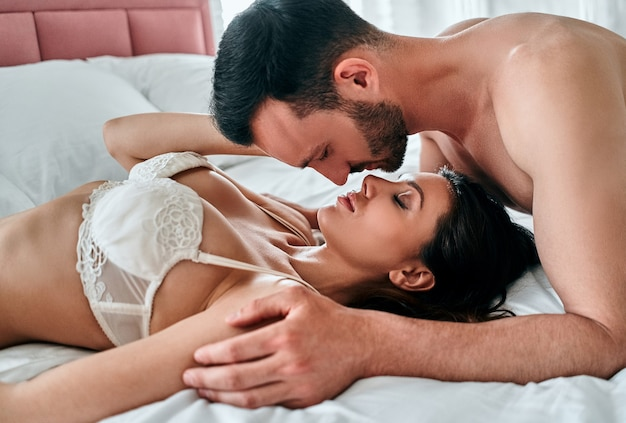 The beautiful man and woman in underwear kissing in the bed