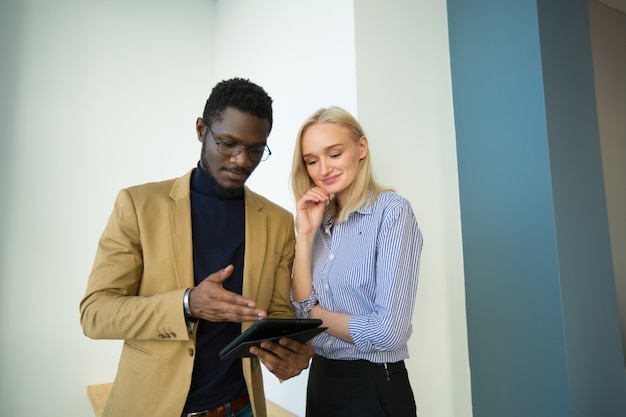 Beautiful man and woman with tablet in the office