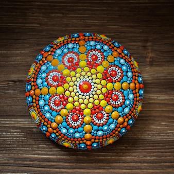 Beautiful mandala rock on wood background