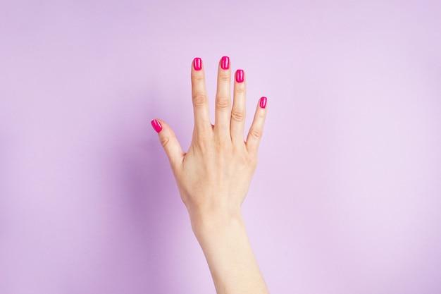 美しいマニキュア。紫色の背景に若い女性の美しい手。
