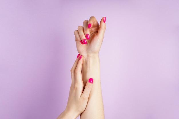 Красивый маникюр. красивые руки молодой женщины на фиолетовом фоне.