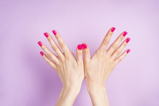 美しいマニキュアのクローズアップ。紫色の背景のフラットに若い女性の美しい手が横たわっていた。