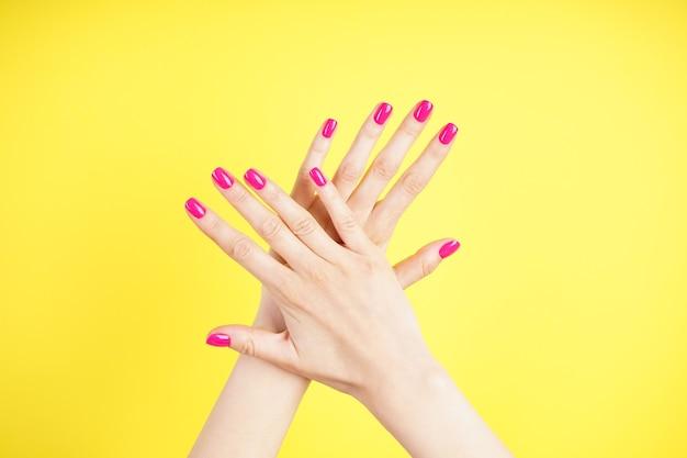 아름다운 매니큐어 클로즈업. 노란색 바탕에 젊은 여자의 아름 다운 손. 평면도
