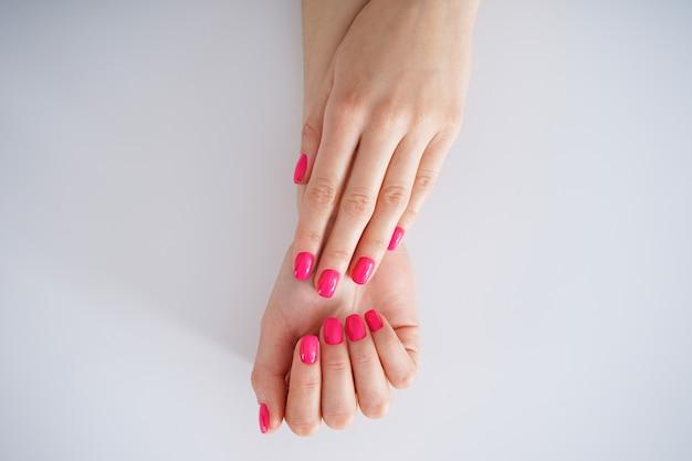 흰색 바탕에 아름 다운 매니큐어입니다. 아름다운 여성의 손. 아름다움과 피부 관리 개념, 평평하다.