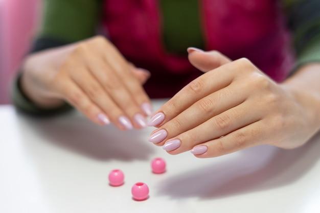 흰색 바탕에 아름 다운 매니큐어입니다. 긴 손톱을 가진 여성의 손. 흰색 바탕에 부드러운 분홍색 매니큐어가 있는 소녀의 손.