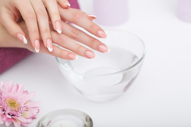 Beautiful manicure with orchid, candle and towel on the white wooden table,