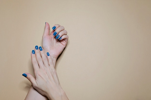 Beautiful manicured woman's nails with classic blue nail polish on beige