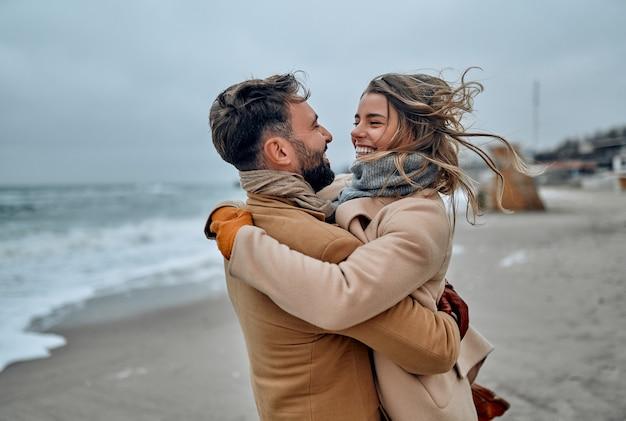 冬にコートを着て、海岸に寄り添う美しい夫婦。