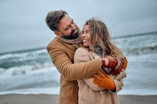 冬にコートを着て、海岸で抱き締める美しい夫婦。