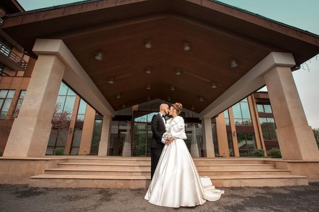 屋外で抱き締める優雅なスーツの美しい夫婦