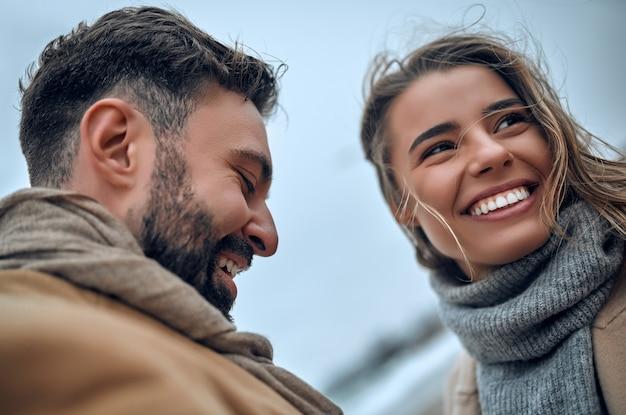 恋をしている美しい夫婦は、冬にコートを着た海岸でお互いを楽しんでいます。