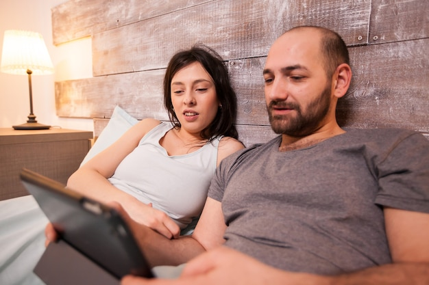 Beautiful married couple in pajamas lying in bed watching tv show on tablet computer.