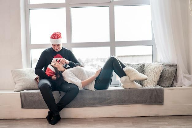 スタジオのソファでポーズをとって美しい夫婦