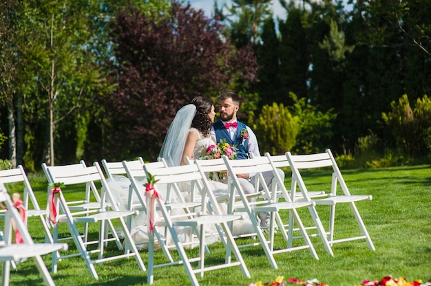 Beautiful married couple sitting one the wedding white wooden chairs for guests