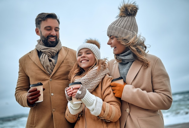 A beautiful married couple and their charming daughter walk on the seashore and drink coffee, dressed in warm clothes.