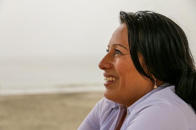 아름다운 성숙한 50세 여성이 바다를 배경으로 웃는다