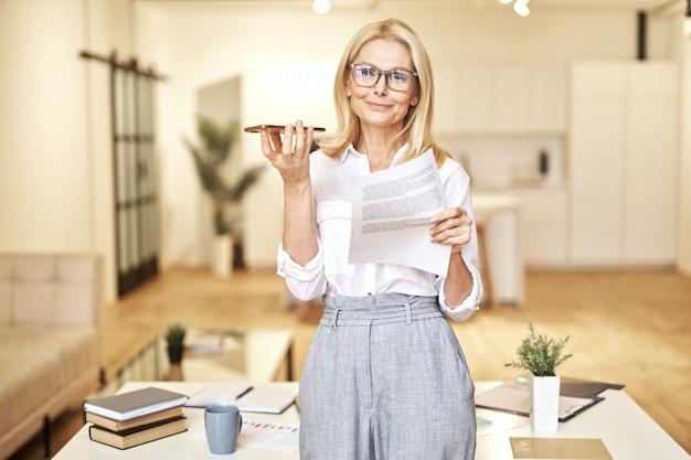 Beautiful mature blonde businesswoman smiling at camera while having call on speakerphone