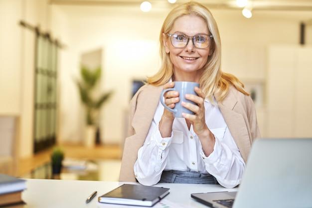 작업하는 동안 카메라를 보고 웃고 커피를 마시는 안경을 쓴 아름다운 중년 여성