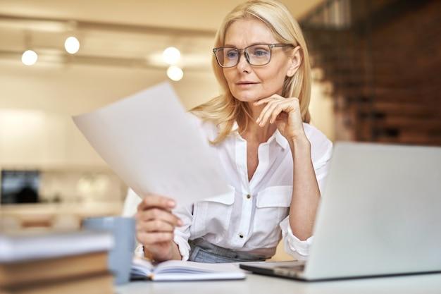 オフィスの机に座ってノートパソコンを使用して論文を読む美しい成熟した実業家