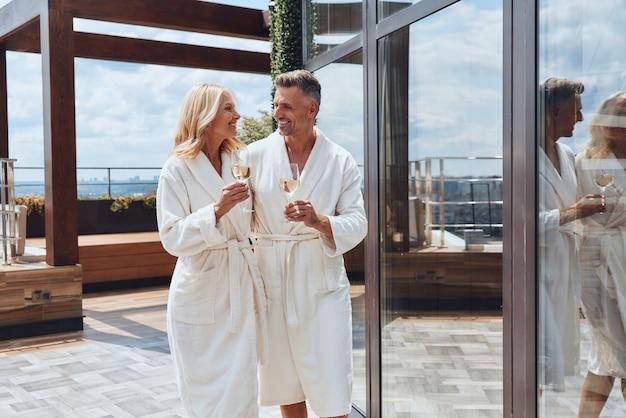 야외 고급 호텔에서 휴식을 취하면서 샴페인을 즐기는 목욕 가운을 입은 아름다운 중년 부부