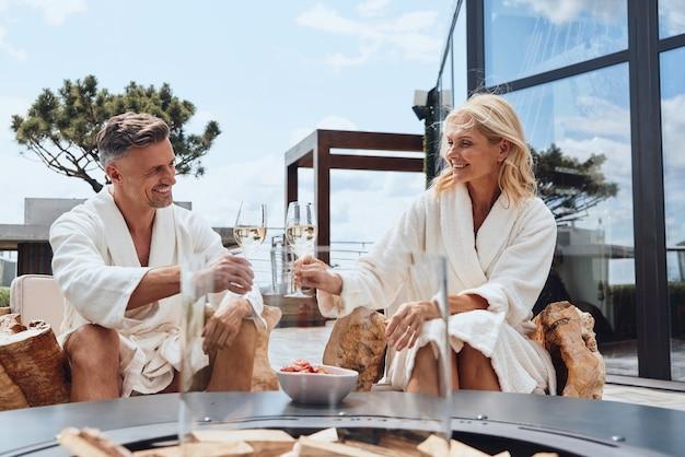 고급 호텔에서 휴식을 취하면서 과일과 샴페인을 즐기는 목욕 가운을 입은 아름다운 중년 부부