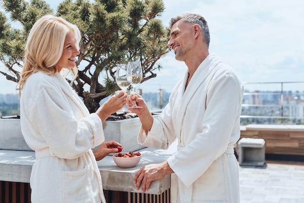 호텔에서 휴식을 취하면서 과일과 와인을 즐기는 목욕 가운을 입은 아름다운 성숙한 커플