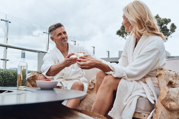 야외 고급 호텔에서 휴식을 취하면서 과일과 와인을 즐기는 목욕 가운을 입은 아름다운 성숙한 커플
