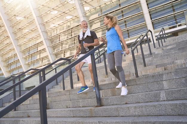 Красивая зрелая пара мужчина и женщина в спортивной одежде вместе тренируются на открытом воздухе