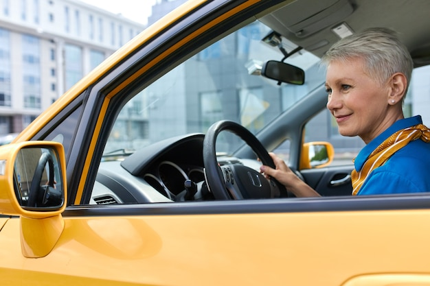 Beautiful mature female with pixie hair driving car, enjoying empty streets early in the morning. attractive middle aged woman sitting in driver's seat, parking automobile, looking at side view mirror