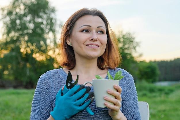 Красивый зрелый садовник в перчатках с секатором с чашкой травяного чая