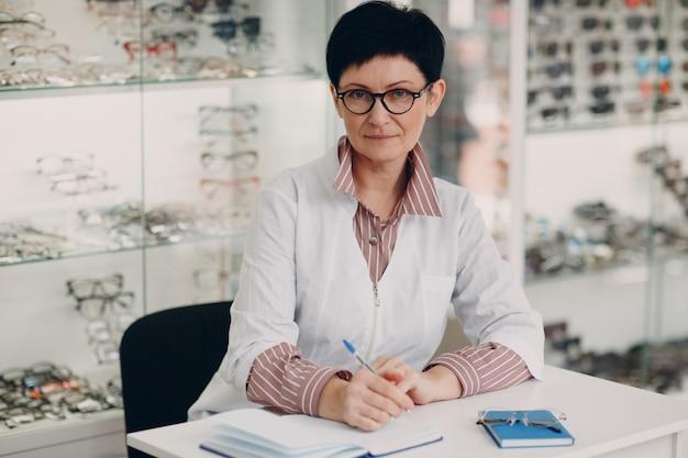 Красивое зрелое сочинительство оптометриста в книге в салоне оптики офтальмологии.