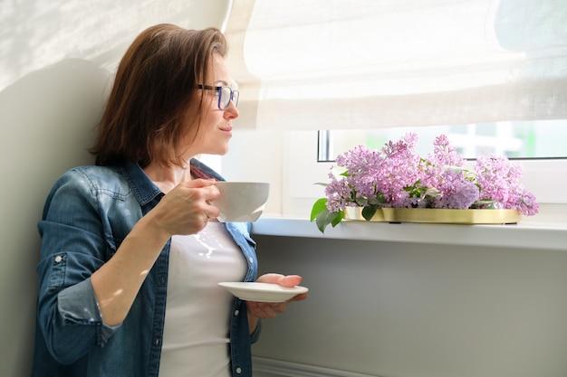 꽃과 함께 집에서 아름 다운 성숙한여 인, 창 근처 여성 서 웃 고