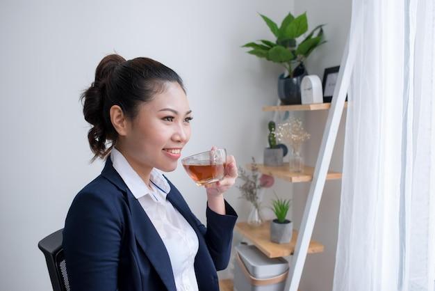 Красивая зрелая женщина, выпивая чашку чая в своем офисе. (с копией пространства.)