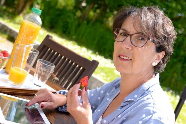 Красивая зрелая женщина ест клубнику, снаружи