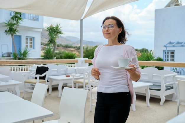 Beautiful mature woman enjoying vacation in resort hotel, in restaurant, view of mountain landscape. female walking with cup of coffee. leisure, summer, weekend, tourism, travel middle-aged people