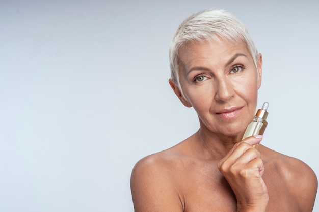 Beautiful mature woman holding face serum in her hand