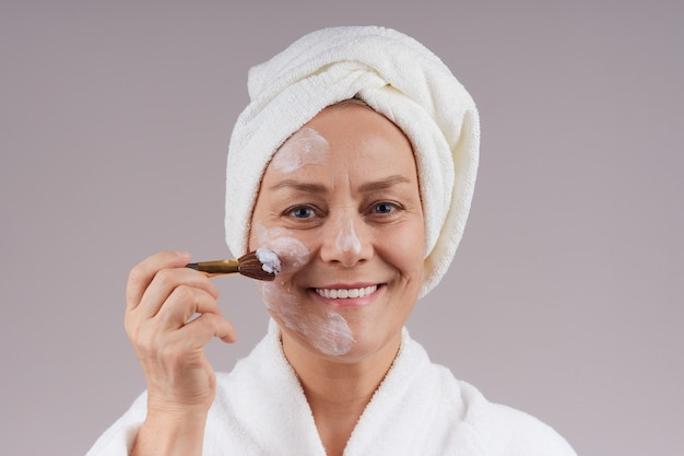 彼女の顔に栄養マスクを適用する白衣の美しい成熟した女性。灰色の壁で隔離します。