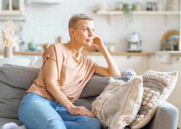 Красивая зрелая женщина в повседневной одежде мечтает о чем-то во время отдыха на диване у себя дома