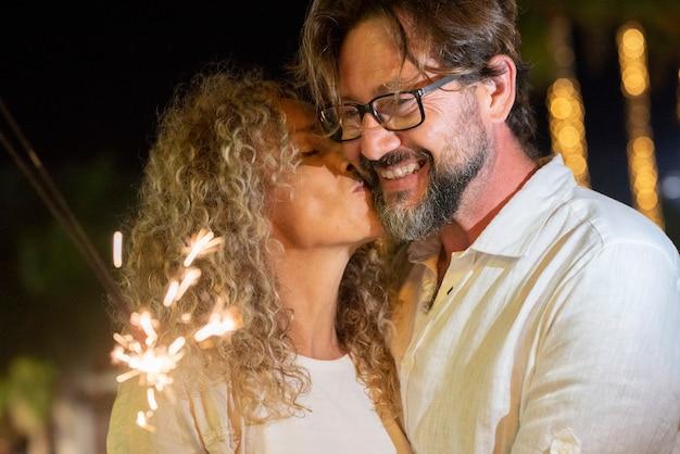 燃える輝きを見ている陽気な男にキスする美しい成熟した女性、ロマンチックな瞬間を楽しんでいるカップル。燃える線香花火と余暇を過ごす愛するカップル