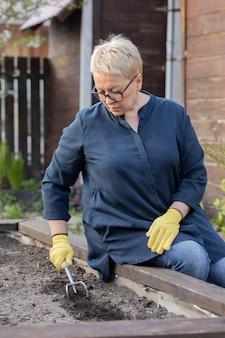 美しい成熟した女性が種を植える前にカルティ鍬で肥沃な土壌を緩める