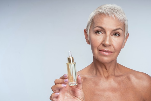 Beautiful mature woman posing with face anti aging serum
