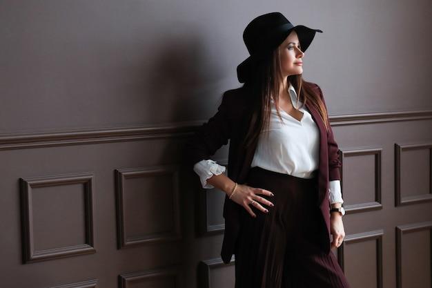 Красивая зрелая женщина позирует с модной одеждой