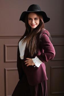 ファッションの服でポーズをとって美しい成熟した女性