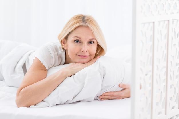 Beautiful mature woman posing with a pillow