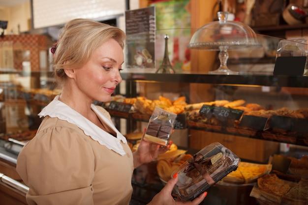 과자 가게에서 쿠키를 쇼핑하는 아름다운 중년 여성