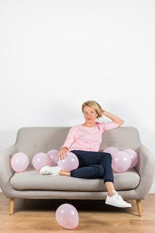 Beautiful mature woman sitting on sofa with pink balloons